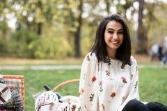 一个相当少妇有野餐在公园,微笑 免版税库存图片