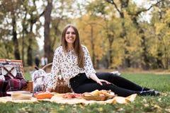 一个相当少妇有野餐在公园,微笑 库存图片