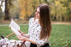 一个相当少妇有野餐在公园,读书 免版税库存照片