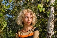 一个相当少妇的画象有一双卷曲金发和蓝眼睛的,站立在桦树附近在公园 库存照片