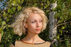 一个相当少妇的画象有卷曲,金发和蓝眼睛的,站立在桦树附近和调查左边 免版税库存照片