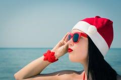 一个相当少妇的画象在圣诞老人帽子和sunglass 库存照片