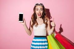 一个相当激动的女孩的画象有五颜六色的购物袋的 库存图片