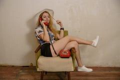 一个相当白肤金发的女孩由电话谈话 免版税库存图片