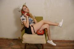 一个相当白肤金发的女孩由电话谈话 免版税图库摄影