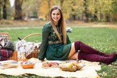 一个相当白肤金发的少妇的画象有野餐在公园 免版税库存照片