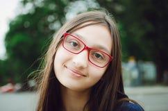 一个相当青少年的女孩的画象戴眼镜的 自然摆在街道上 免版税库存图片