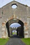 一个看法通过主教` s Mussenden议院的被成拱形的庭院门下坡私有地的 免版税库存照片