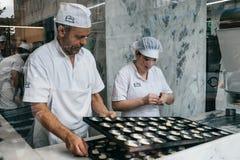 一个看法通过咖啡馆的作为厨师的窗口或玻璃准备称葡萄牙式奶油挞的一个传统葡萄牙点心 免版税库存照片