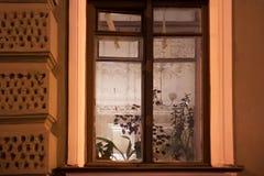 一个看法通过对公寓的老破旧的窗口与在天花板的一种富有的回纹装饰 库存照片