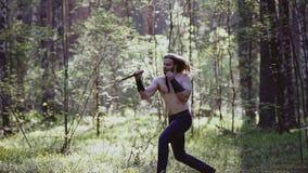 一个真正的北欧海盗战士进行在森林尼斯射击的训练刀子罢工在长的焦点 股票视频