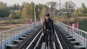 一个真正的顽固的家伙横跨往照相机的桥梁走并且注视着斜向一边日落 股票视频