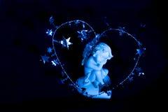 一个睡觉天使的小雕象在蓝色背景的 免版税库存图片