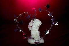 一个睡觉白色天使的小雕象在红色背景的 免版税库存照片