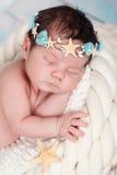 一个睡觉的新出生的女孩的接近的画象海星和珍珠海箍的  免版税库存图片