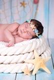 一个睡觉的新出生的女孩的接近的画象海星和珍珠海箍的  库存图片