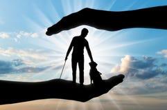 一个瞎的残疾人的剪影有藤茎的在他的手和狗指南上 免版税库存照片