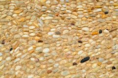 一个石墙、路从小在周围和卵形石头的纹理与沙子与自然老黄色黑褐色缝  背景 免版税库存照片