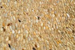 一个石墙、路从小在周围和卵形石头的纹理与沙子与自然老黄色黑褐色缝  背景 库存图片