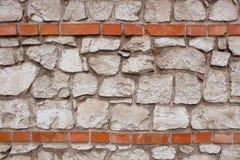 一个石墙由与两条红砖水平线的白色石头块做成 免版税库存图片