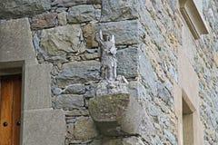 击败一个石大厦的背景的天使雕塑敌人在Rupit 库存照片