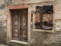 一个石房子的被风化的老门和快门在茨雷斯岛 免版税库存照片