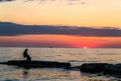 一个石海滩的孤独的渔夫在日落背景 免版税图库摄影