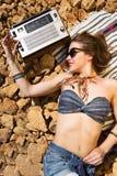 一个石海滩的美丽的女孩 免版税库存照片