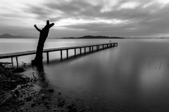 一个码头的长的曝光视图在一个湖的,有移动的云彩和p的 库存图片