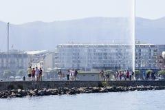 一个码头的游人对著名喷泉在莱芒湖,瑞士 库存照片