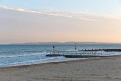 一个码头的金黄日落光在一个海滩的与沙子和没有云彩在天空在一个海滩在欧洲 免版税库存照片
