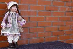 一个砖墙的背景有玩偶立场的 免版税库存图片