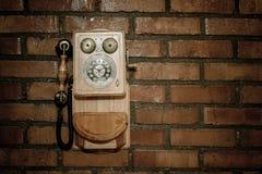 一个砖墙的难看的东西都市背景有一个老在服务范围外投币式公用电话的 免版税库存图片