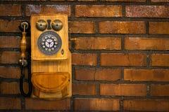 一个砖墙的难看的东西都市背景有一个老在服务范围外投币式公用电话的 库存图片