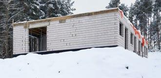 一个砖房子的未完成的工地工作在冬天冻森林里 库存照片