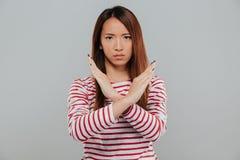 一个确信的亚洲妇女陈列的画象横渡了手势 库存照片