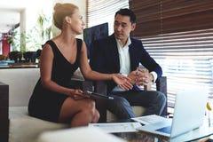 一个确信的人和妇女企业家的画象谈论企业想法,当坐在办公室空间时 免版税库存图片