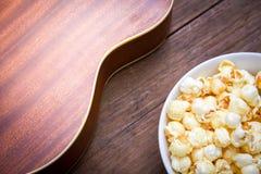 一个碗玉米花和尤克里里琴在一张木桌上 库存照片