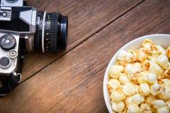 一个碗玉米花和照相机在一张木桌上 库存图片