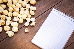 一个碗玉米花和笔记本在一张木桌上 图库摄影