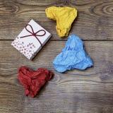 一个礼物箱子和三张五颜六色的心形的被弄皱的纸在木桌上 华伦泰` s 恋人` s天 库存图片