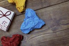 一个礼物箱子和三张五颜六色的心形的被弄皱的纸在木桌上 华伦泰` s 恋人` s天 图库摄影
