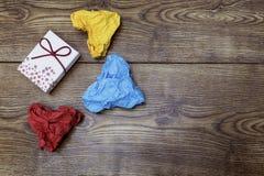 一个礼物箱子和三张五颜六色的心形的被弄皱的纸在木桌上 华伦泰` s 恋人` s天 免版税库存图片