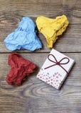 一个礼物箱子和三张五颜六色的心形的被弄皱的纸在木桌上 华伦泰` s 恋人` s天 免版税库存照片
