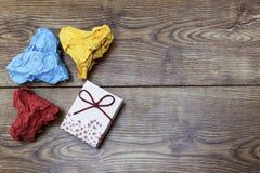 一个礼物箱子和三张五颜六色的心形的被弄皱的纸在木桌上 Valentine& x27; s Lover& x27; s天 免版税库存图片