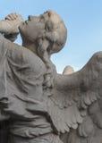 一个祈祷的天使的石雕塑 库存照片