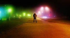 一个神奇人在街道单独站立,在汽车中在一个空的城市,步行夜街道,梦想 库存照片
