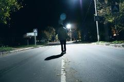 一个神奇人在街道单独站立,在汽车中在一个空的城市,步行夜街道,梦想 库存图片