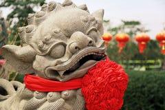一个神话动物的石雕象与一把红色弓的在泰国 图库摄影
