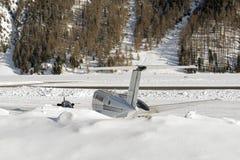 一个私人喷气式飞机的背面图在积雪的机场在阿尔卑斯瑞士在冬天 免版税库存照片